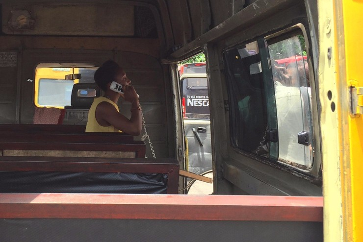 Making a call with a DanFone handset aboard one of Lagos' Danfo buses